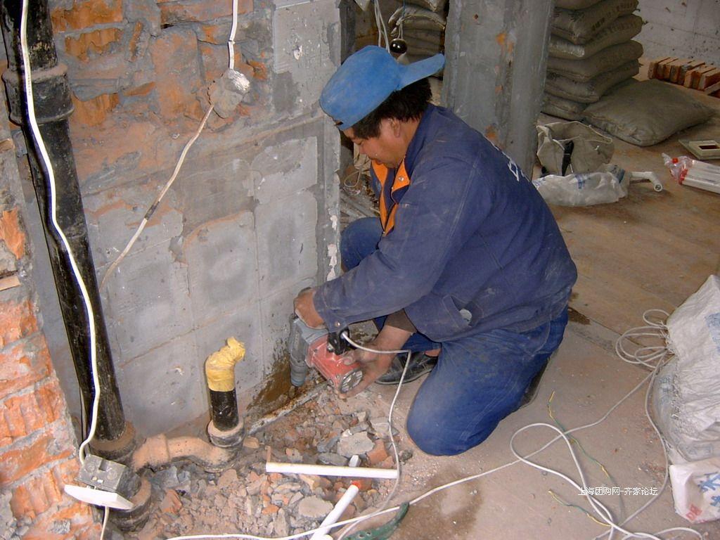 装潢工人冷热管开槽和走向需绕道围绕卫生间顶部转一圈.现...